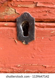 Closeup of black painted metal key hole on red painted wooden barn door with peeled paint and copy space.