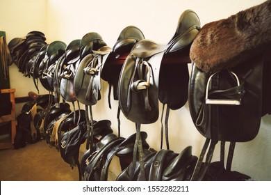 Close-up of black Saddles in tack room