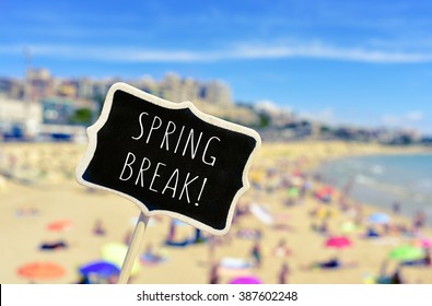 closeup of a black signboard with the text spring break written in it, in front of a blurred beach with many people bathing and sunbathing