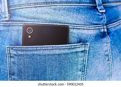 closeup of Black smartphone in back pocket of girl's jeans