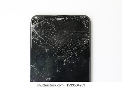Closeup of black smartphone with broken screen on white blackground