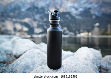Close-up black of steel eco thermo water bottle on the background of the lake in the mountains. Copy space. Zero waste, no plastic, sustainability.