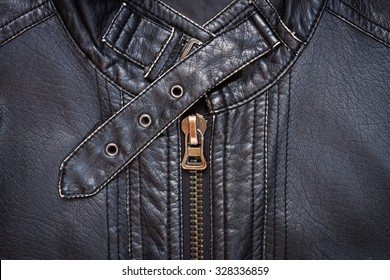 Close-up of black synthetic leather jacket showing a zipper and a collar belt