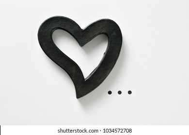 closeup of a black three-dimensional heart and points of ellipsis on a white background, with some blank space around them