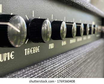Close-up black treble knob volume on the control panel of the boutique electric guitar amplifier. clean and hi-gain distortion for the rock to metal, blues, and jazz genres. Music business concept.