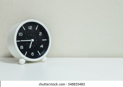 Closeup black and white alarm clock for decorate in a quarter to seven or 6:45 a.m. on white wood desk and cream wallpaper textured background with copy space