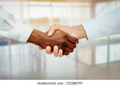 Close-up of a black and white hands shaking over a good business agreement.