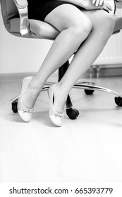 Closeup black and white photo of of businesswomen feet in ballet flats under office table