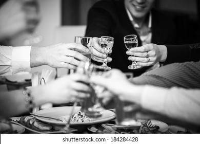 Closeup black and white photo of hands clinking glasses at restaurant