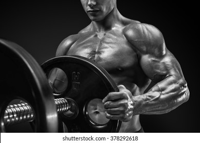 Closeup black and white photo of handsome bodybuilder guy prepare to do exercises with barbell in a gym, keep barbell plate in hands