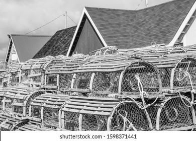 A closeup, black and white photo of high stacks of traditional wooden lobster traps beside an old shed in a fishing village.