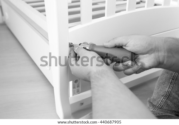 Closeup black and white photo of man tightening the screws on furniture with screwdriver