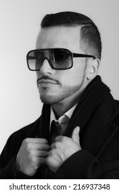 Closeup black and white portrait of handsome elegant young hispanic man wearing suit and sunglasses