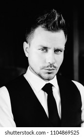 Close-up black and white portrait of stylish athletic ofiice man in a business owner costume vest. Sitting on the chair. In a suit with a tie and a vest. piercing and atmospheric model look.