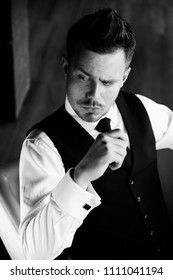 Close-up black and white portrait of stylish athletic ofiice man in a business owner costume vest. Sitting on the chair. In a suit with a tie and a vest.