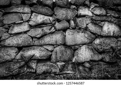 Closeup of black and white rock stone wall outdoors. Old vintage grunge texture structure.