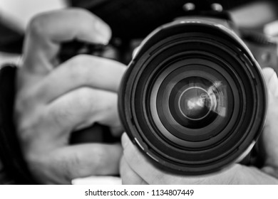 Close-up black and white shot of crop hands holding professional photo camera and taking pictures