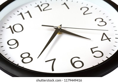 Closeup of black and white wall clock with three hands isolated over white.