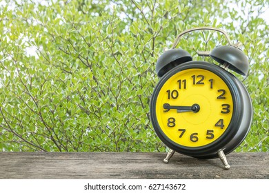 Closeup black and yellow alarm clock for decorate show a quarter to nine o'clock or 8:45 a.m. on old brown wood desk on green leaves in the park textured background