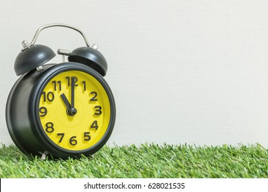 Closeup black and yellow clock for decorate in 11 o'clock on green artificial grass floor and cream wallpaper textured background with copy space