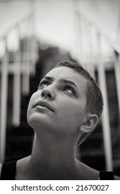 Close-up black-and-white portrait of a beautful teenager girl looking upside and thinking. Stairs on the background