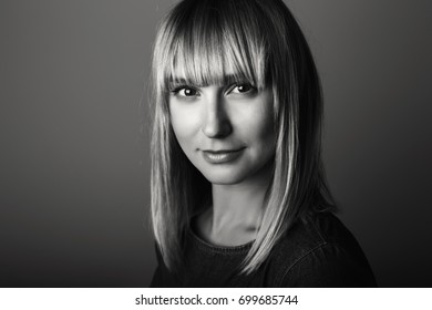 Closeup black-and-white portrait of beautiful young middle age blonde Caucasian woman looking in camera. Girl female with long blonde hair bob, studio beauty shot.