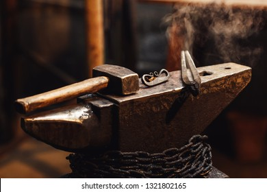 closeup of a blacksmith anvil with a hammer, tongs and firesteel
