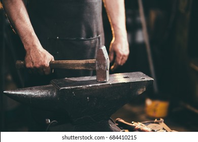 Close-up of blacksmith manually forging the molten metal on the anvil in smithy workshop. Blacksmith working metal with hammer in the forge