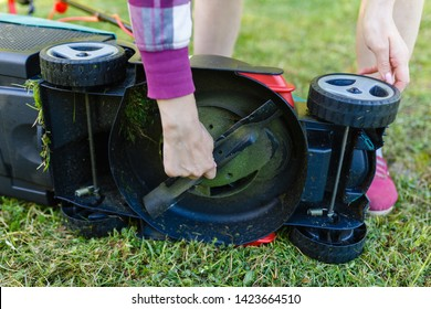 Close-up of the blade is a modern electric lawn mower on the grass in the yard. The girl removes the stuck grass from the blades of the lawn mower