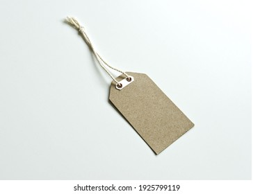 Closeup of blank brown cardboard price tag isolated on white background. Brown cardboard label.