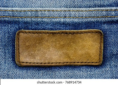 Closeup blank brown leather label on vintage blue jeans. The old tag on the back of pants. Leather patch and stitch on denim fabric. Suitable for backgrounds, articles about fashion clothing.
