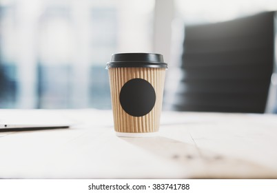 Closeup of blank craft paper coffee cup on the wood table. Space for you advertising. Horizontal mockup, blurred background