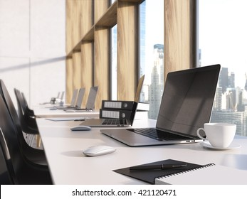 Closeup of blank laptop screen on desktop with coffee cup, documents and other items in coworking office with new York city view. modern office with laptop on table. Mock up, 3D Rendering