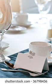 A closeup of a blank wedding placecard in front of a coffee cup, and other items on the table.