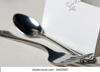 A closeup of a blank wedding placecard with a spoon and fork in front, showing detail of the table cloth.