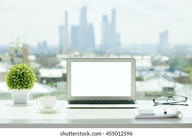 Closeup of blank white laptop on windowsill with a coffee cup, glasses, notepad with pen, smartphone and decorative plant on blurry city background. Mock up