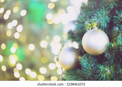 Closeup of blond bauble hanging from a decorated christmas tree on blurred of lights with decorated tree, sparkling and bokeh background. copy space for your text.