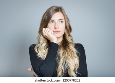 closeup of a blond woman bored, isolated over gray background