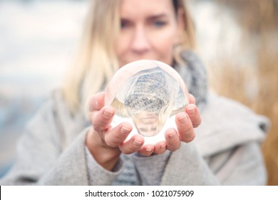 closeup of blond woman holding up a glass ball