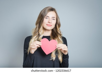 closeup blond woman holding heart - symbol of love, isolated over gray background