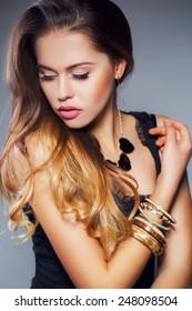 closeup of blond woman with long wet curly hair wearing pink lipstick. Beautiful blonde brunette woman. Studio shot