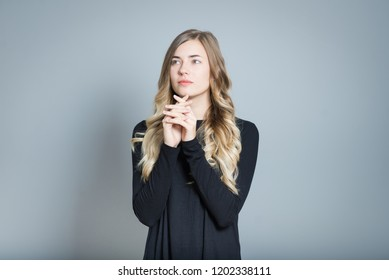 closeup blond woman praying or meditating, silence and harmony, isolated over gray background