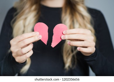 closeup blond woman tearing heart in half, isolated over gray background