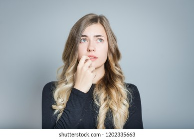 closeup blond woman worries and bites her nails, isolated over gray background
