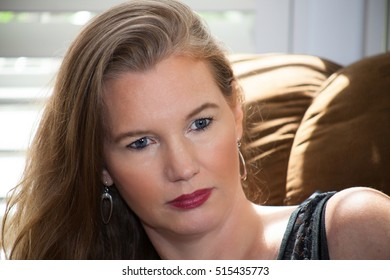 Closeup of Blonde Female On Couch Looking Expressionless