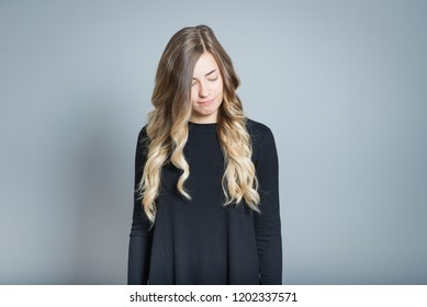 close-up blonde woman guilty and ashamed isolated over gray background
