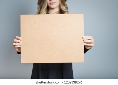 closeup of a blonde woman holding a cardboard for inscriptions, isolated over gray background