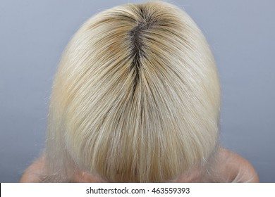 Close-up of a blonde woman's head with unpainted regrown roots
