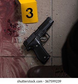 Close-up of blood and gun - evidence of murder