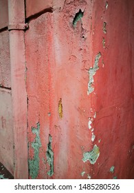 closeup of blood red damaged and weathered painted plastered wall